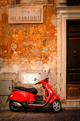 Typical scene with a red scooter on a narrow central Rome street