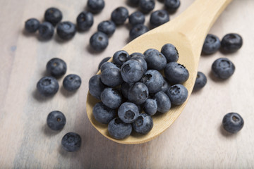 CloseUp Of Fresh Blueberries on a wooden spoon