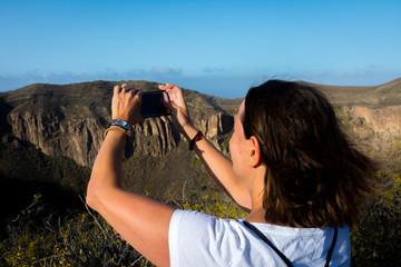 Mujer sacando foto de volcán en Gran Canaria, España con teléfono móvil