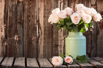 Pink roses in a green bucket style container on a wooden plank table.