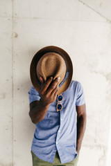 Stylish man covering face with hat