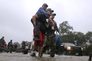 An elderly man is carried after being rescued from the flood waters of tropical storm Harvey in east Houston