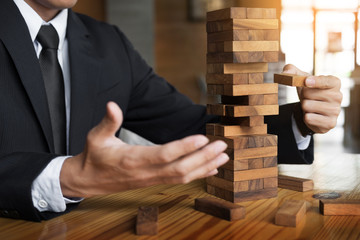 Planning, risk and wealth strategy in business concept, businessman and insurance gambling placing wooden block on a tower