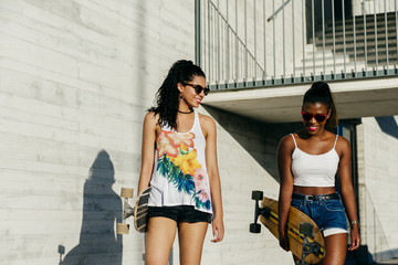 Young women with boards at street