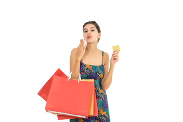 Young beautiful woman with credit card in hand and holding shopping bags over white background