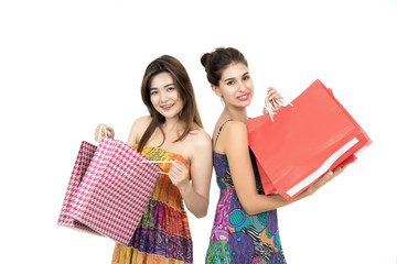Young two woman carrying shopping bags isolated on white.