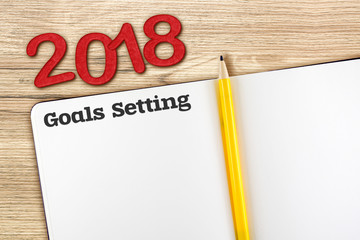 Top view of 2018 new year red number and goals setting with blank open notebook and yellow pencil on wooden table top,Mock up for adding your content or design.