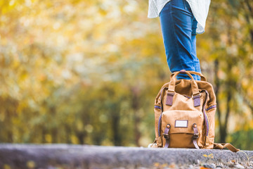 Close up backpack of woman backpacker standing on countryside road with tree in autumn fall seasonal,Alone travel or single traveller concept