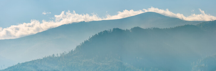 clouds rising behind the blue mountain