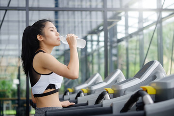 Asian woman drinking water on wellness in sport gym.