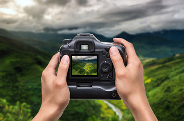 Hands holding the camera which taking photo of Rice fields on terraced of Mu Cang Chai District at sunrise time, YenBai province, Northwest Vietnam, worm tone