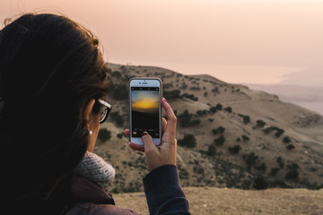 Pretty woman watching the sunset in the desert and photographing with a smartphone