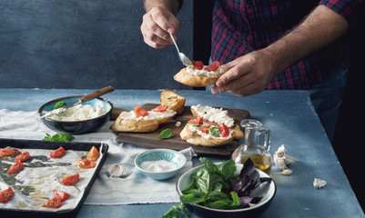 Man cooking bruschetta with baked tomato, cheese and garlic