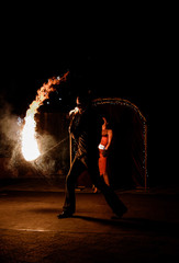 Man dances with fire outisde in the night
