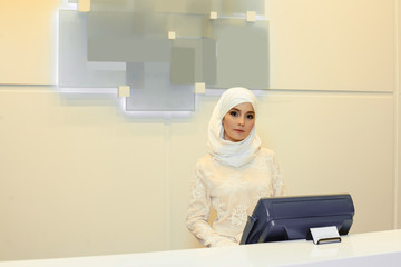 Beautiful Muslim woman standing behind the reception in the hotel