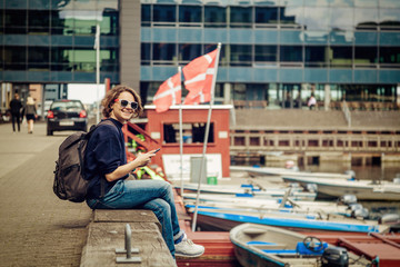 Young woman traveler sits on the waterfront in Copenhagen overlooking the canal with a mobile phone in hands