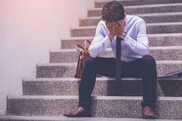 stressed businessman with headache sitting at stairway. disappointed for job search