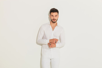 fashion man in white clothes fixing sleeve