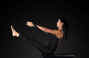 Professional pilates reformer instructor performing teaser pose