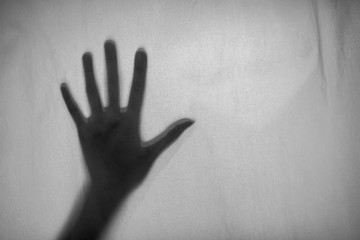 Black and white photo Shadow of hand the white Blinds,fear, help, horror and scary.