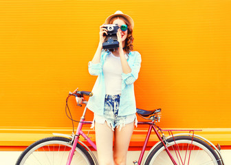 Summer fashion woman with retro camera and bicycle on a colorful orange background