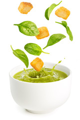 spinach leaves and croutons falling into a soup bowl