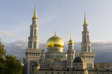 White crescent moon and domes of the Moscow Cathedral Mosque in the evening reflect sunlight.