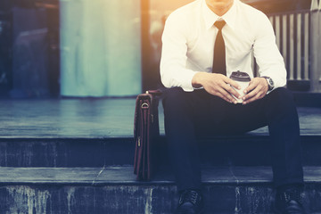 Businessman sitting in front of company building with hope concept.