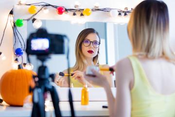 blogger woman applying cosmetics at camera