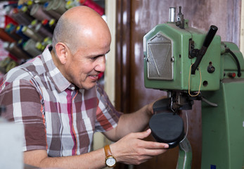 Elderly specialist stitching shoes on leather sewing machine