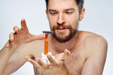 Man holds a razor and shaving foam, portrait