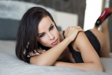 Sexy brunette woman lying on bed