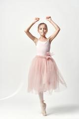 Little girl ballerina on a light background