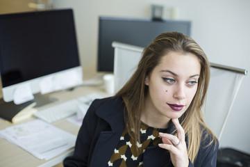 Bella Segretaria, seduta nella scrivania del suo ufficio, persa nei sui pensieri