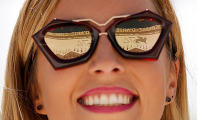 The logo of the 74th Venice Film Festival is seen reflected in the sunglasses of a woman in Venice