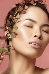 Beautiful asian woman with fresh daily makeup. Vietnamese beauty girl in spa treatment with green leafs near face