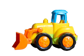 Small yellow toy tractor isloated on white