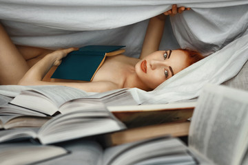 Young redhead naked girl in bed at home bedroom reading book, covered with a blanket. Many books in the foreground