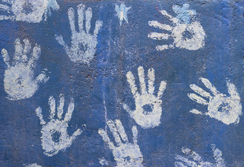White paint handprints on a blue wall
