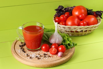Fresh tomato juice in a glass mug. A mug of tomato juice and fresh tomatoes on a green wooden background.