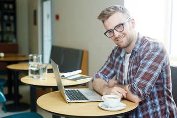 Happy designer in eyeglasses and casualwear networking by cup of coffee in cafe