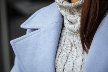 Closeup detail of women's clothing. The girl in a warm sweater and coat