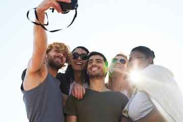 Low angle view of cheerful young friends with toothy smiles taking picture of themselves on camera while hanging out at outdoor party, lens flare