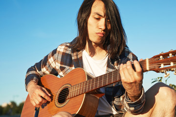 Portrait of confident Asian man wearing checked shirt playing guitar while sitting outdoors, cloudless blue sky on background
