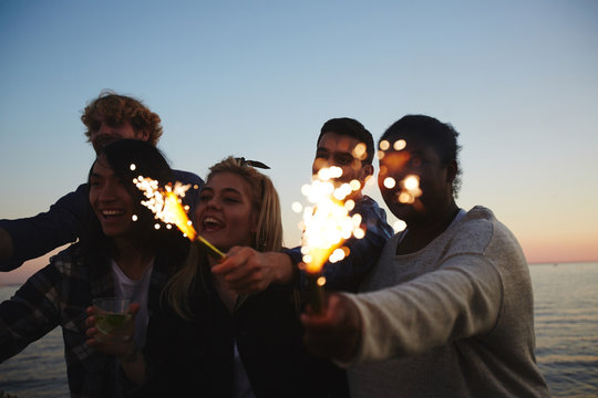 Male and female friends with sparklers in hands gathered together outdoors and celebrating momentous event, picturesque seascape on background