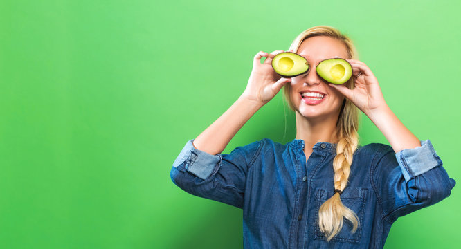 Happy young woman holding avocado halves on a green background