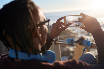 Man holding phone taking picture of beautiful seaside ocean scen