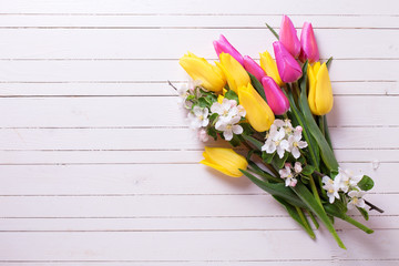 Bunch of bright yellow and pink spring tulips and apple tree flowers  on white  wooden background.