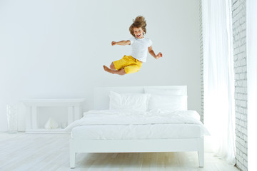 The child is jumping on the bed