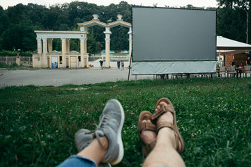 couple lies on the ground and watch movie in open air cinema